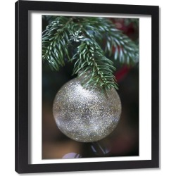 Framed Print. Silver, glittery bauble suspended from Christmas tree branch