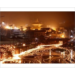 Photograph. Oil lamps offered by devotees illuminate the Bagmati River flowing through the premises